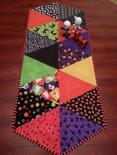 I have used 100% high quality cotton fabric on this cute table runner. The colors are perfect for your halloween decorating. There are cute candy corn, ghosts & black cats in this fun fabric. The backing is black fabric and the binding is a fun black and orange stripe which is machine attached and then hand stitched by me. I have quilted the triangles in a modern outline shape. **Finished size is 16 1/2 inches wide by 40 inches long** Machine wash gentle in warm water with mild...