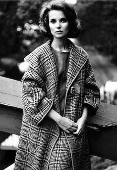 1962 Bonnie Trompeter in wool Glen plaid coat with suede piping and large shawl collar with buckle fastener worn over matching skirt and suede top by Bonnie Cashin