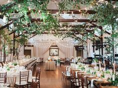 Wedding reception in the Granary with hanging greenery, candles, and matching table runners at Pippin Hill Farm & Vineyards | PHOTOG: Luna De Mar | PLANNER - Cody with Amore Events | Video - East West | Ceremony Musicians - Plum Trio | Band - Soul Fusion | Floral - Amy Osaba | Cake - Sweethaus | AV and Lighting - BRAVL | Transpo - Blue Ridge Tours | Rentals - Festive Fare and MS Events