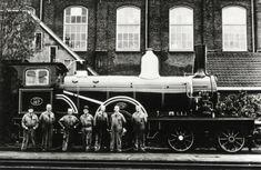 Afbeelding van de stoomlocomotief nr. 107 van de N.R.S., gerestaureerd ten behoeve van het spoorwegmuseum door gepensioneerd personeel van de Centrale Werkplaats van de N.S. te Tilburg, met van links naar rechts de heren Schilders, Brekelmans, De Bats, De Rooy, Peling, Van Stokkem en Put. 1953