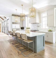 Three gold hexagon lanterns illuminate a long, gray kitchen island topped with honed white marble fitted with a prep sink lined with vintage bar stools placed atop rustic plank floors. Home Decor Kitchen, New Kitchen, Home Kitchens, Rustic Kitchen, Kitchen Interior, Kitchen Ideas, Shaker Kitchen, Modern Kitchens, Green Kitchen