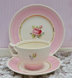 Beautiful tea cup and saucer made from from porcelain or pottery. The likely manufacture period is 1950s-1960s. The cup and saucer are lovely antique white porcelain decorated with a pink rose on cup and plate with a delicate border of pink complimented by a band of gilding around the centre of the plate and saucer. The cup has a fine line of gilding around the cup and on the inside of the cup. The rear of the cup is decorated with a little rosebud spray. The cup and saucer are in excellent…