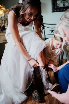 Bride puts on her brown leather cowboy boots with the help of her flower girl and bridesmaid on wedding day / Rustic Bride / LEB is weekend wedding destination & barn event venue located in the Texas Hill Country / Photo: EffJay Photography