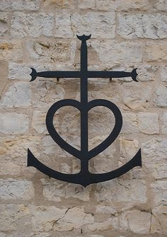 The Camargue cross on the wall of the church in Saintes-Maries-de-la-Mer, France. The combination of the 3 shapes: cross, heart and anchor, are meant to symbolize faith, hope and love.