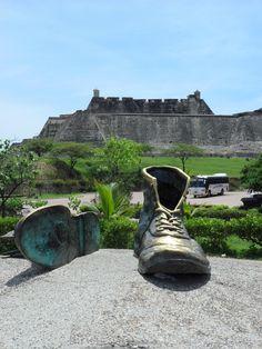Monumento a los Zapatos Viejos... al fondo: El Castillo de San Felipe. - Cartagena, Colombia