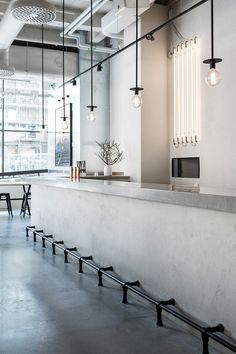 concrete bar, neat pendant lights, also fluorescent line lights in back - love!   Courtesy of Richard Lindvall