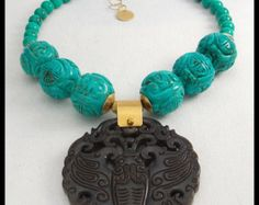 Intricately detailed, handmade brass/copper/silver Tibetan repousse prayer box pendant hangs from necklace made of 2 strands of aventurine tubes and round jade beads accented by brass Bali style spacers. Prayer box has inlay of jade and I have added jade bead topped by handforged bronze bead cap to bottom of pendant. Necklace fastens with my signature, large, fancy handforged bronze clasp and soldered link brass chain. Adj from about 19 - 21 inches.