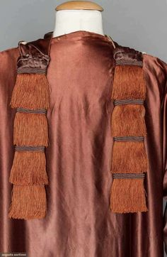 1917 Eggplant silk charmeuse, white silk charmeuse lining, wide sleeves w/ rust thread ball buttons from shoulders to rust fringed sleeve hem, wide F panel wraps over right shoulder, 2 fringed tabs fall to back at shoulders,