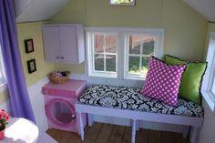 Intérieur d'une cabane pour enfants en bois, aménagée avec une banquette et une mini machine à laver