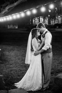 Photo of bride and groom under stringed lights by campfire on wedding day by Alysha Christine Photography