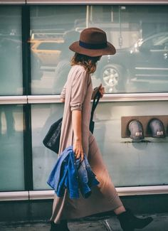 For a day at the city she is wearing a simple Maxi dress, hat, and short boots. Fashion inspiration to copy.