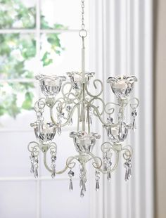 Gorgeous crystal flowers bloom to create a romantic lighting feature for your favorite room. The ivory metal scroll work holds six clear candle cups as dramatic faceted jewels hang down to capture the