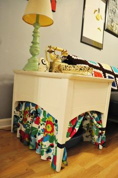 Placing the litter box under a table is a good start, but adorable patterned curtains really hide it from sight.