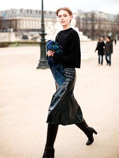 Frida Gustavsson is snapped in a midi black patent skirt paired with tall boots during Fashion Week
