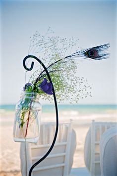 Details : Adorable decoration for the beach composed of some greenery, violet flowers and a peacock feather (by Aquadeco) - Emily & Rishi's destination wedding in Tulum