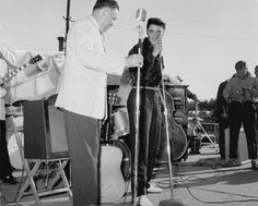 Elvis on stage in Tupelo, actor Nick Adams filming on the right.