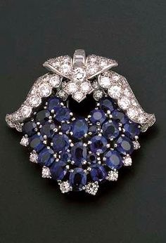 AN ART DECO SAPPHIRE AND DIAMOND CLIP BROOCH, BY CARTIER Designed as a triple-row of cushion-cut sapphires with baguette-cut and pavé-set diamond winged surmount, circa 1930, 3.5 cm. high, in original Cartier red leather fitted caseSigned Cartier London, no. 116486
