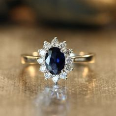 This halo diamond + blue sapphire engagement ring is a stunner.