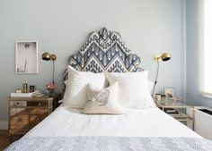 Chic blue bedroom features a pale blue wall lined with a blue ikat Headboard with brass nailhead trim on bed dressed in white and blue bedding flanked by mismatched nightstands illuminated by antique brass sconces.