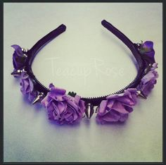 This is a unique lilac spike headband is made using a black headband covered in black ribbon which lilac roses with silver metal spikes have then been attached to. There are six roses and seven spikes in total.