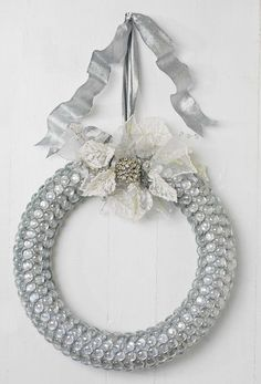 Holiday Wreath - 1. Wrap a Styrofoam wreath form with silver fabric ribbon. 2. Using a hot-glue gun, attach clear glass florist's beads in rows, starting from the inside of the circle. 3. Tie on ribbon for hanging. 4. Embellish with objects that add sparkle: small ornaments, a rhine-stone brooch, little jingle bells, bird figures, or whatever strikes your fancy