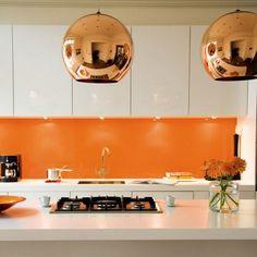 Kitchen with whote cabinetry, backlit orange splashback and copper pendant lights