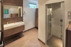 Deze warme en luxe badkamer is ingericht met badkamermeubels van Custom Made De Jong en heeft een Sunshower in de douche. Een badkamer om volledig in te ontspannen.