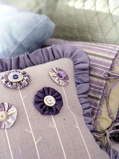 Button Flowers  Add pretty little flowers to a plain pillow by using the quilter's yo-yo technique. Stitch around small fabric circles. Pull the thread end to gather the circles into poufs. Use pearl cotton and a stem stitch to make the stems and leaves; attach the poufs for blossoms. Sew a button to each blossom center.
