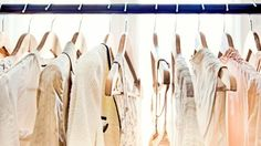 A row of light-colored clothing secured on wooden hangers is visible from about armpit level up, dangling from a rod which stretches from one end of the frame to the other. Behind the rack, two large windows brighten the room with daylight.