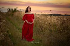 Maternity photography Yorkshire Leeds, Bradford, York, Harrogate, Wakefield: beautiful pregnant woman in red dress walking through the countryside before the sunset