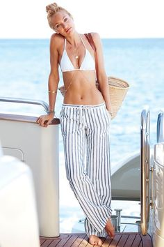 Perfect beach / yacht vacation style - loose striped linen pants, white string bikini top and straw tote bag - Candice Swanepoel
