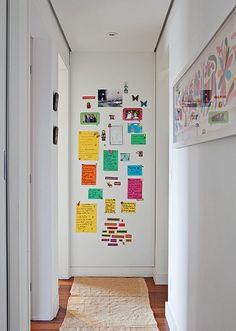 A parede final do corredor tem placa metálica para ímãs, onde ficam expostos recados e fotos. Projeto da designer de interiores Maristela Gorayeb