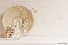 Soft home decor of glass vase with spikelets and knitted fabric on white wood background.