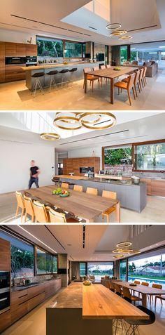 A void in the ceiling with circular pendant lights helps to anchor the dining table in the open plan room. Behind the dining area is the kitchen with a large grey island with a wood bar for sitting at. Wood cabinets line the wall and a large sliding window looks out onto the garden.