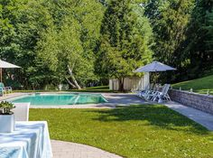 Outside, rolling lawns and lush trees are nestled next to stone walls and an pool.