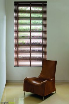 Luxury wooden blinds and a contemporary brown leather chair.