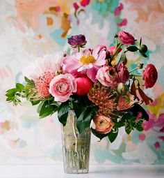 bright flowers in a tall vase with abstract background
