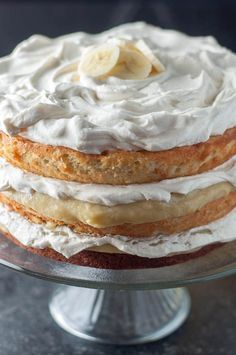 This Fluffy Banana Cake with Fresh Banana Curd Filling recipe has light, fluffy banana cake layers, a fresh banana curd filling, and whipped cream frosting. www.mamagourmand.com