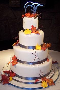 Round, four tier Fall wedding cake design, embellished with yellow, burnt orange and dark red Autumn leaves. And decorated with silver ribbon around each tier and a monogram wedding cake topper. From www.tiffanysbakingco.com               #wedding #cake #birthday