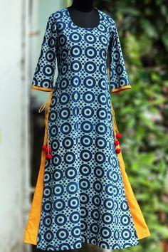 a long kurtain layers with handblock printedindigo fabric & pop coloured inner layer. the layered kurta has tie-ups and woolen fumdas to add to the pop!