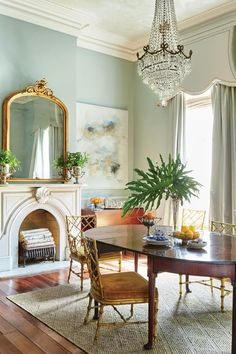 """Match History with Glamour - A New Orleans Renovation that Captures History and Charm - Southernliving. """"Sticking with one period, one color, or one style can come across as staid and serious,"""" says Kaynor. So instead, she plucked feminine pieces from different eras, placing gilt Hollywood Regency chairs alongside 100-year-old marble mantels and a grand crystal chandelier. The wide wooden floors and dark table provide enough old-house seriousness to keep it from looking like a movie set…"""