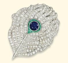 AN EARLY 20TH CENTURY SAPPHIRE, DIAMOND AND EMERALD BROOCH   Designed as a pierced 'peacock' feather mounted with single-cut diamonds to the circular-shaped sapphire decoration and calibré-cut emerald accents, circa 1920