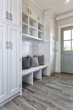 Gray wood-grain tile sets the tone in this fabulous mud room with floor-to-ceiling built-in closets.
