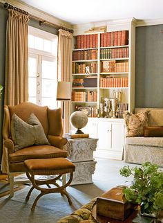 Den/library with grey upholstered walls, tan wing chair, white bookcases, and globe --- Interior design: Roger Higgins and Ann Shipp, R. Higgins Interiors, rhigginsinteriors.com --- Photo: Reid Rolls --- Traditional Home