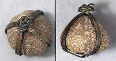 Galerites-stenkerne indfattet i bronzetråd. Amulet eller smykke. Fundet ved Lindholm Høje, Nørresundby. Vikingetid.