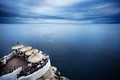 Cova d'en Xoroi en Menorca, Islas Baleares. Las cuevas del moro, en castellano, es una terraza-discoteca esculpida en el interior de una gruta natural y sobre un impresionante acantilado que da al mar. Deben su nombre a una antigua leyenda de la isla y se pueden visitar tanto de día, para ver una espectacular puesta de sol, como durante la noche, para bailar y tomar un cocktail bajo la luna. Un lugar único en el mundo.