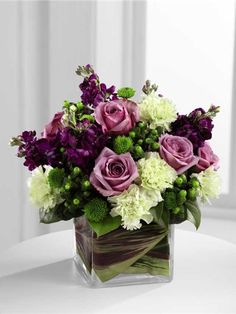 Compact leaf lined cube vase of purple flowers and green flowers