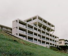 The building appears as a reticular structure perched above the railway, on the hills facing Lake Lugano, containing 14 dwellings behind its concrete envelope. As a project, it is driven by a reflection on the lifespan of materials and how they can enable a transformation over a 50-100 year cycle.