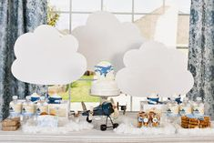 Aviation themed baby shower with dessert table that has clouds & mini airplanes hanging above.