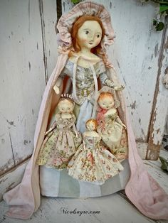 """Nicol Sayre Doll Shoppe: Mary has gathered all her little flower maids from the Garden. Is dressed in a skirt of antique faded stripe twill w/a bodice of antique french cotton. Around her waist is a striped belt w/embossed metal buckle. Her cloak is an antique baby/doll cape of glazed cotton lined w/ flannel & trimmed in ribbon. Her little maids, 6"""" & 8"""" are dressed in delicate floral cottons w/wee antique lace petticoats & pantalets. She is paper mache w/wool hair 22"""". 18-Apr-2018"""
